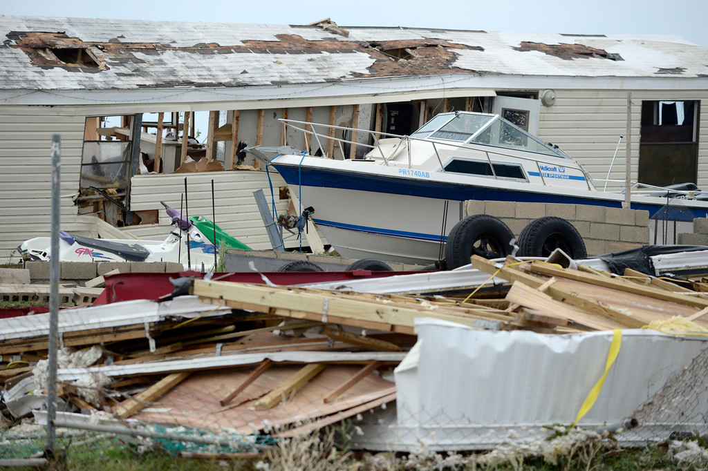 . A pleasure boat stands next to a destroyed home after the passing of Hurricane Irma, in Culebra, Puerto Rico, Thursday, Sept. 7, 2017. About a million people were without power in the U.S. territory after Irma passed just to the north, lashing the island with heavy wind and rain. Nearly 50,000 also were without water. (AP Photo/Carlos Giusti)