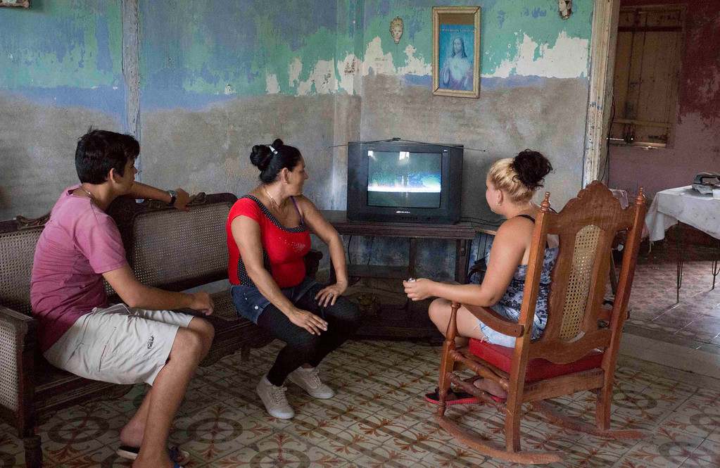 . Residents watch a televised weather forecast hours before the arrival of Hurricane Irma, in Caibarien, Cuba, Friday, Sept. 8, 2017. Cuba evacuated tourists from beachside resorts after Hurricane Irma left thousands homeless on a devastated string of Caribbean islands and spun toward Florida for what could be a catastrophic blow this weekend. (AP Photo/Desmond Boylan)