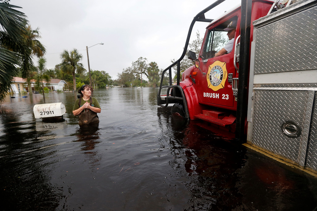 . Firefighters check on Kelly McClenthen, who returned to check on the damage to her flooded home, in the aftermath of Hurricane Irma in Bonita Springs, Fla., Monday, Sept. 11, 2017. (AP Photo/Gerald Herbert)
