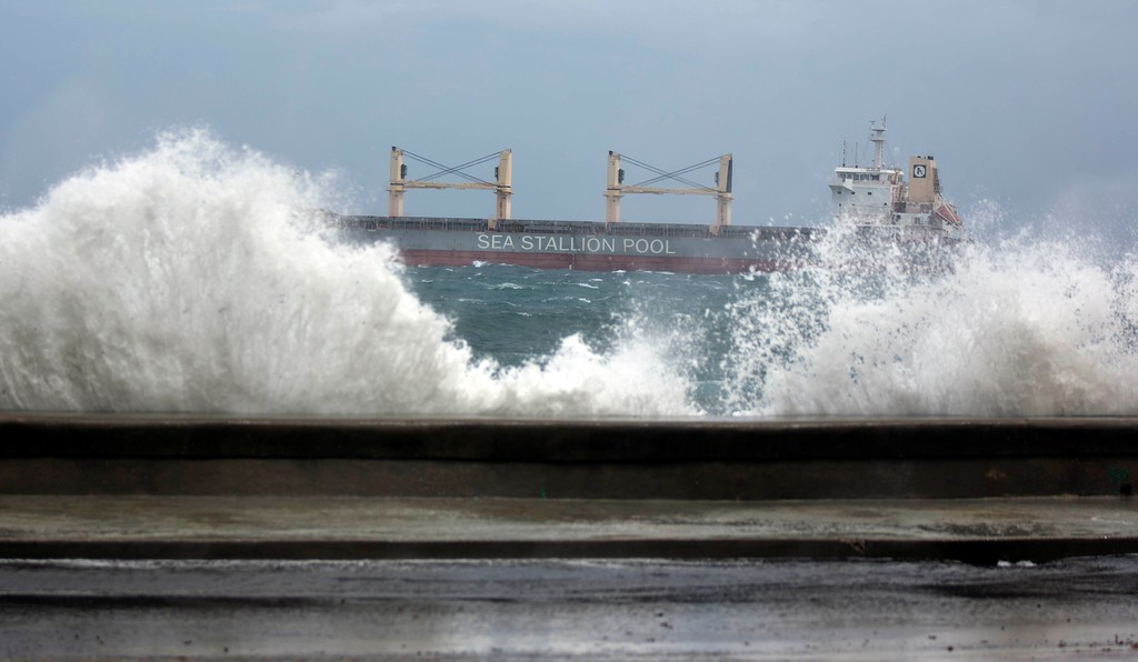 . A sea wall is breeched by overflow as a bulk carrier leaves the bay of Havana, Cuba, Saturday, Sept. 9, 2017. There were no reports of deaths or injuries after heavy rain and winds from Hurricane Irma lashed northeastern Cuba. (AP Photo/Ramon Espinosa)