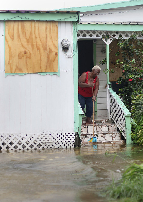 . A woman pushes out floodwaters on her property after the passing of Hurricane Irma, in St. John\'s, Antigua and Barbuda, Wednesday, Sept. 6, 2017. Heavy rain and 185-mph winds lashed the Virgin Islands and Puerto Rico\'s northeast coast as Irma, the strongest Atlantic Ocean hurricane ever measured, roared through Caribbean islands on its way to a possible hit on South Florida. (AP Photo/Johnny Jno-Baptiste)