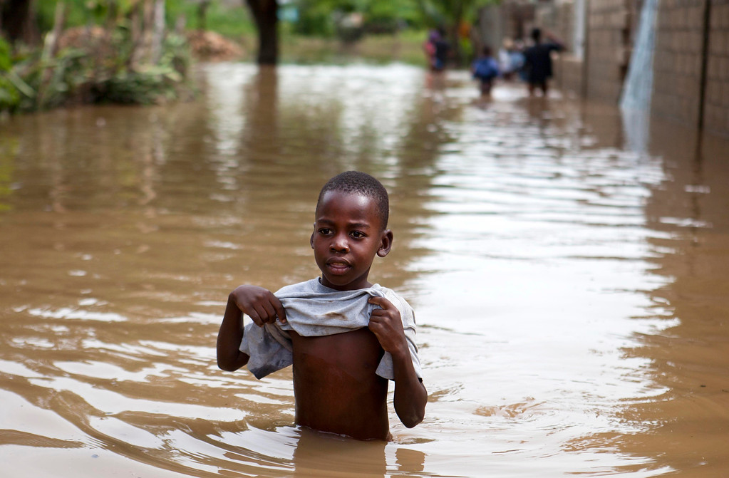 . A boy walks in the floodwaters of Hurricane Irma, in Fort-Liberte, Haiti, Friday Sept. 8, 2017. Irma rolled past the Dominican Republic and Haiti and battered the Turks and Caicos Islands early Friday with waves as high as 20 feet (6 meters). ( AP Photo/Dieu Nalio Chery)