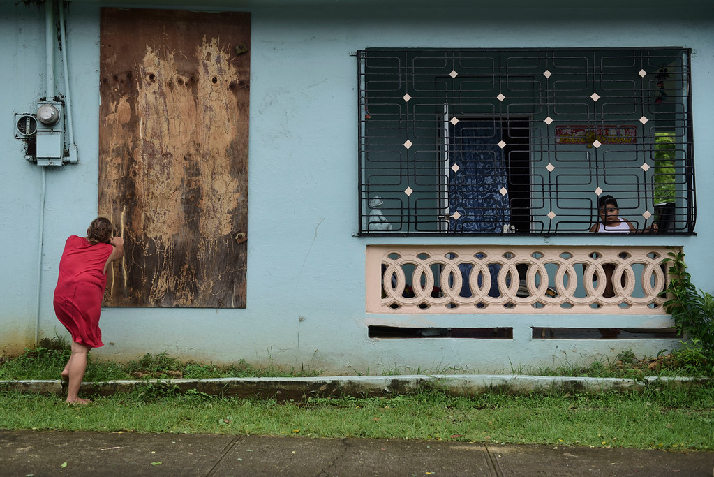 . A woman boards up a window in preparation for Hurricane Irma, in Ceiba, Puerto Rico, Wednesday, Sept. 6, 2017. Irma roared into the Caribbean with record force early Wednesday, its 185-mph winds shaking homes and flooding buildings on a chain of small islands along a path toward Puerto Rico, Cuba and Hispaniola and a possible direct hit on densely populated South Florida. (AP Photo/Carlos Giusti)
