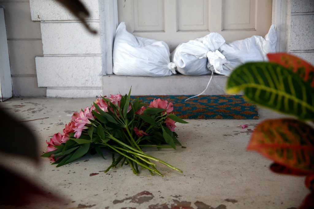 . ST PETERSBURG, FL -  SEPTEMBER 9:  A resident leaves flowers on her front porch next to sandbags as she loads her vehicle to  comply with a mandatory evacuation ahead of Hurricane Irma on September 09, 2017 in St. Petersburg, Florida. Florida is in the path of the Hurricane which may come ashore at  category 4.  (Photo by Brian Blanco/Getty Images)