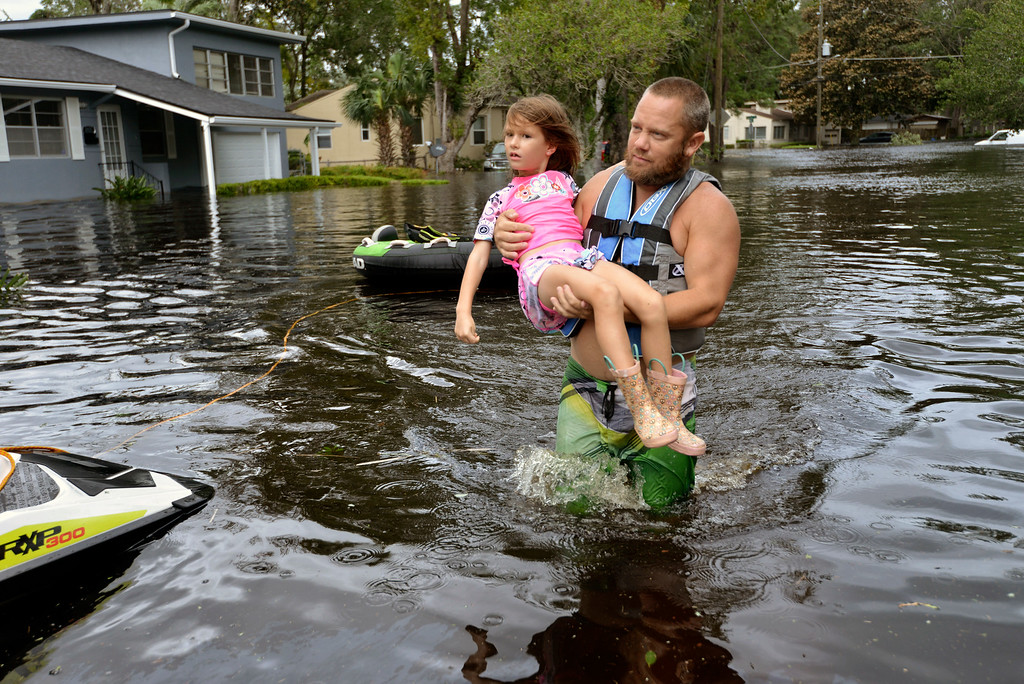 . Tommy Nevitt carries Miranda Abbott, 6, through floodwater caused by Hurricane Irma on the west side of Jacksonville, Fla., Monday, Sept. 11 2017. (Dede Smith/The Florida Times-Union via AP)