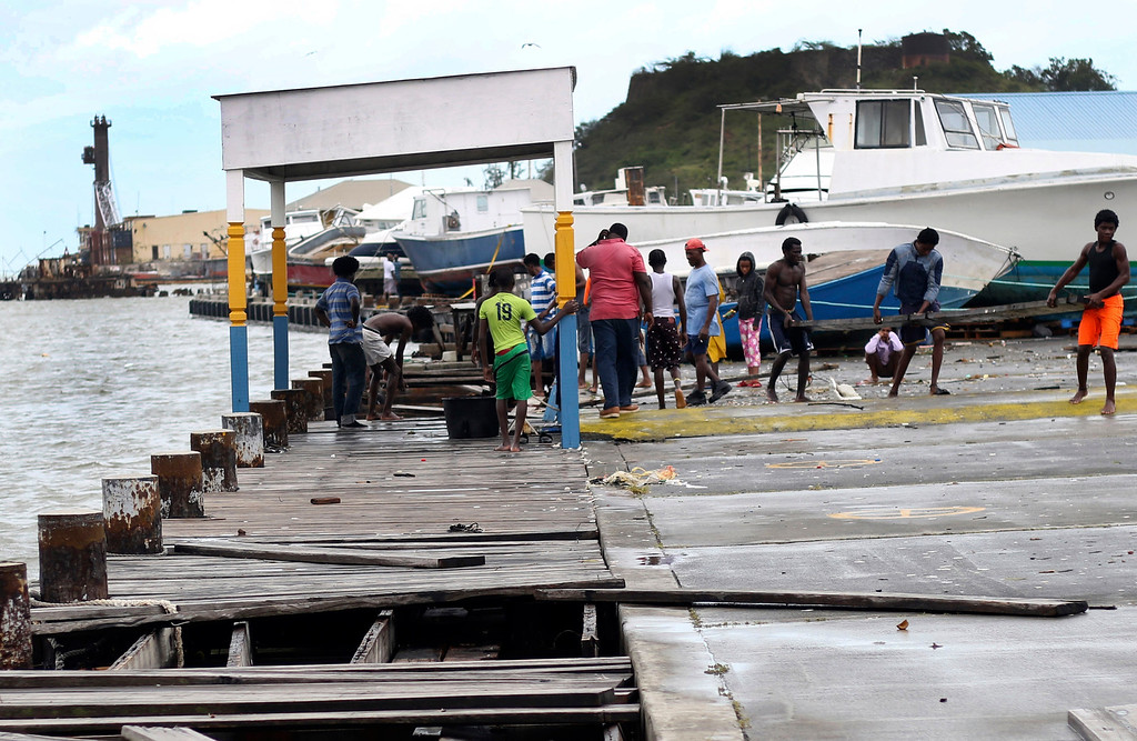 . People recover broken parts of the dock after the passing of Hurricane Irma, in St. John\'s, Antigua and Barbuda, Wednesday, Sept. 6, 2017. Heavy rain and 185-mph winds lashed the Virgin Islands and Puerto Rico\'s northeast coast as Irma, the strongest Atlantic Ocean hurricane ever measured, roared through Caribbean islands on its way to a possible hit on South Florida. (AP Photo/Johnny Jno-Baptiste)