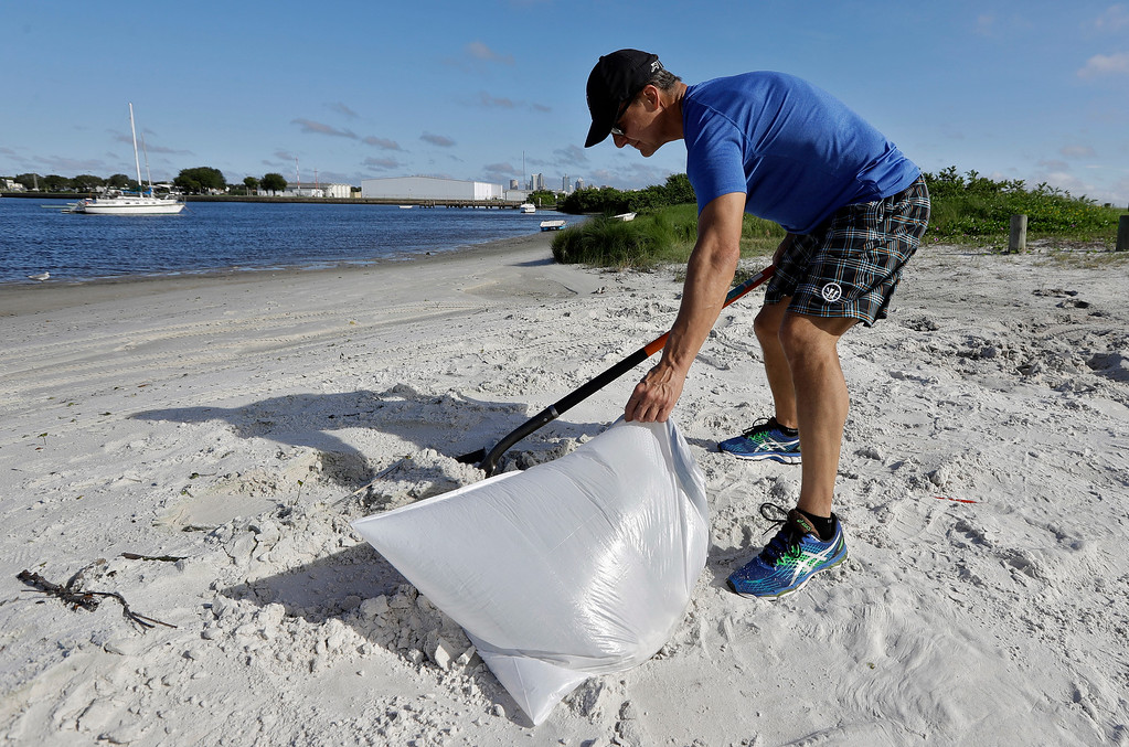 . Troy Mollohan, of Tampa, Fla., fills sand bags along the beach at the Davis Islands yacht basin Saturday, Sept. 9, 2017, in Tampa, Fla. Residents along Florida west coast are making preparations for the arrival of Hurricane Irma. (AP Photo/Chris O\'Meara)