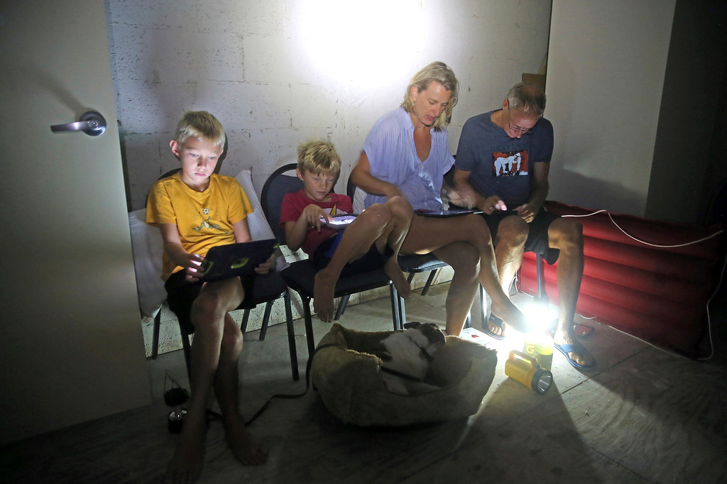 . The Blinckman family use their personal devices while sheltering in a stairwell utility closet as Hurricane Irma goes over Key West, Fla., Sunday, Sept. 10, 2017. Hurricane Irma made landfall near Cudjoe Key as a Category 4 hurricane. (Charles Trainor Jr/The Miami Herald via AP)