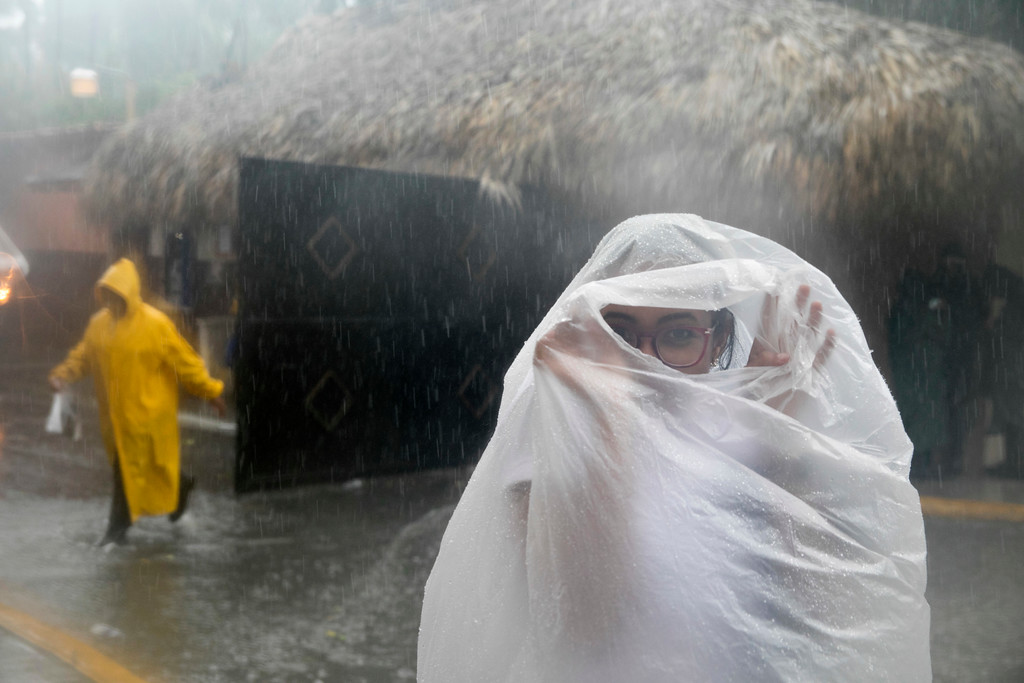 . A woman covers herself with a plastic bag as she makes her way to work as Hurricane Maria approaches the coast of Bavaro, Dominican Republic, Wednesday, Sept. 20, 2017. (AP Photo/Tatiana Fernandez)