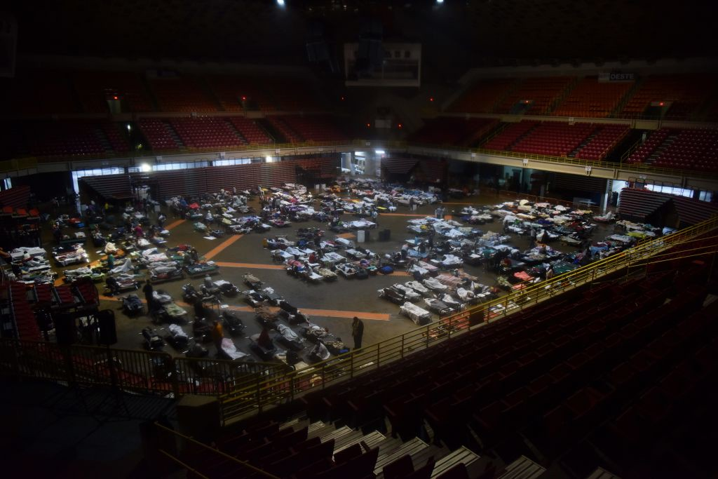 ". Residents seek shelter inside Roberto Clemente Coliseum in San Juan, Puerto Rico, early on September 20, 2017, as Hurricane Maria passes the island. Hurricane Maria closed in on the Virgin Islands and Puerto Rico on September 20 as forecasters warned of a ""potentially catastrophic\"" storm that has already killed at least two people in the Caribbean. / AFP PHOTO / HECTOR RETAMAL        (Photo credit should read HECTOR RETAMAL/AFP/Getty Images)"