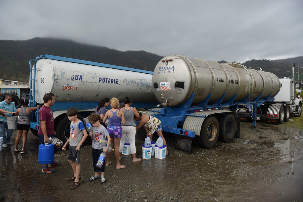 . Locals arrive at a water collection point a day after the impact of Hurricane Maria, in Yabucoa, Puerto Rico, Thursday, September 21, 2017. As of Thursday evening, Maria was moving off the northern coast of the Dominican Republic with winds of 120 mph (195 kph). The storm was expected to approach the Turks and Caicos Islands and the Bahamas late Thursday and early Friday. (AP Photo/Carlos Giusti)