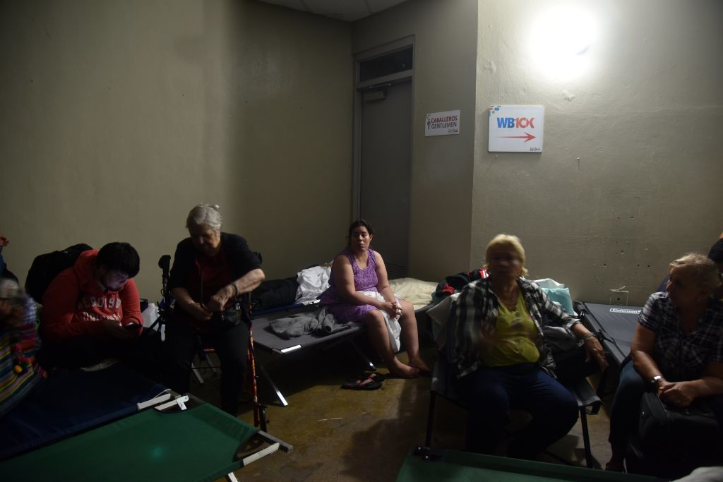 """. People take shelter at Roberto Clemente Coliseum in San Juan, Puerto Rico, on September 20, 2017, during the passage of the Hurricane Maria. Maria made landfall on Puerto Rico on Wednesday, pummeling the US territory after already killing at least two people on its passage through the Caribbean. The US National Hurricane Center warned of \""""large and destructive waves\"""" as Maria came ashore near Yabucoa on the southeast coast. / AFP PHOTO / HECTOR RETAMAL        (Photo credit should read HECTOR RETAMAL/AFP/Getty Images)"""
