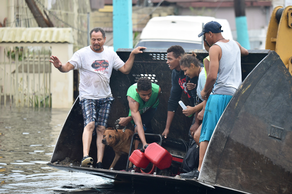 . People are transported down a road flooded by Hurricane Maria in Juana Matos, Catanon, Puerto Rico, on September 21, 2017. Puerto Rico was facing dangerous flooding and an island-wide power outage on Thursday following Hurricane Maria as the death toll from the powerful storm topped 15 in the tiny Caribbean island of Dominica. (HECTOR RETAMAL/AFP/Getty Images)