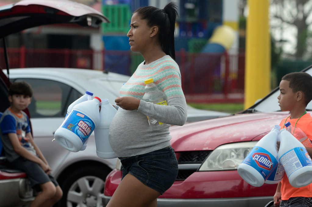 . A pregnant woman carries empty plastic bottles to collect water a day after the impact of Hurricane Maria, in Yabucoa, Puerto Rico, Thursday, September 21, 2017. As of Thursday evening, Maria was moving off the northern coast of the Dominican Republic with winds of 120 mph (195 kph). The storm was expected to approach the Turks and Caicos Islands and the Bahamas late Thursday and early Friday. (AP Photo/Carlos Giusti)