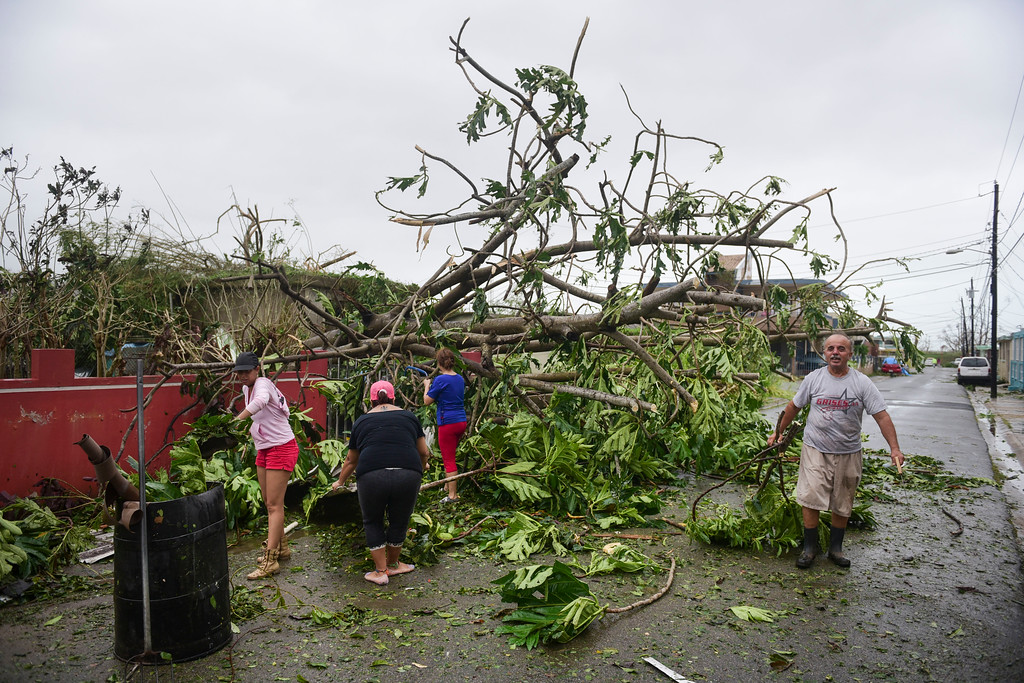 . A family helps clean the road after Hurricane Maria hit the eastern region of the island, in Humacao, Puerto Rico, Tuesday, September 20, 2017. The strongest hurricane to hit Puerto Rico in more than 80 years destroyed hundreds of homes, knocked out power across the entire island and turned some streets into raging rivers in an onslaught that could plunge the U.S. territory deeper into financial crisis. (AP Photo/Carlos Giusti)