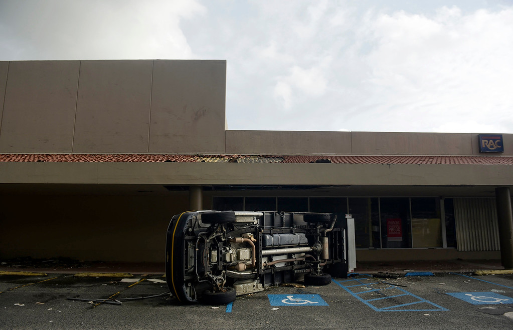 . An overturned vehicle stands in a parking lot after the passing of Hurricane Maria, in Yabucoa, Puerto Rico, Thursday, September 21, 2017. As of Thursday evening, Maria was moving off the northern coast of the Dominican Republic with winds of 120 mph (195 kph). The storm was expected to approach the Turks and Caicos Islands and the Bahamas late Thursday and early Friday. (AP Photo/Carlos Giusti)