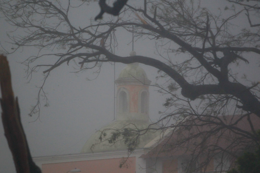 """. The top of a church is seen through branches as Hurricane Maria hits Puerto Rico in Fajardo, on September 20, 2017. Maria made landfall on Puerto Rico on Wednesday, pummeling the US territory after already killing at least two people on its passage through the Caribbean. The US National Hurricane Center warned of \""""large and destructive waves\"""" as Maria came ashore near Yabucoa on the southeast coast. / AFP PHOTO / Ricardo ARDUENGO        (Photo credit should read RICARDO ARDUENGO/AFP/Getty Images)"""