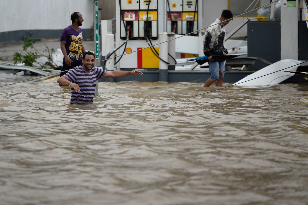 . People walk next to a gas station flooded and damaged by the impact of Hurricane Maria, which hit the eastern region of the island, in Humacao, Puerto Rico, Wednesday, September 20, 2017. The strongest hurricane to hit Puerto Rico in more than 80 years destroyed hundreds of homes, knocked out power across the entire island and turned some streets into raging rivers in an onslaught that could plunge the U.S. territory deeper into financial crisis. (AP Photo/Carlos Giusti)