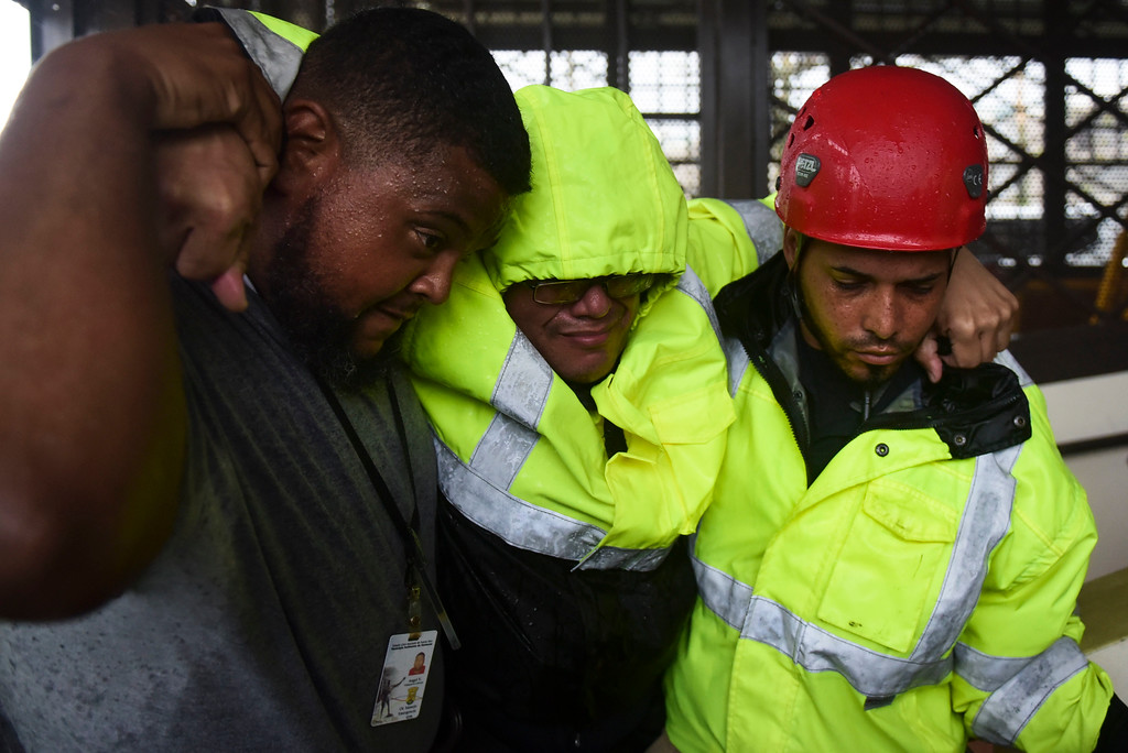 . A municipal police officer arrives at the Emergency Management Agency after being removed from their flooded station by rescue personnel during the impact of Hurricane Maria, which that hit the eastern region of the island, in Humacao, Puerto Rico, Wednesday, Sept. 20, 2017. The U.S. National Hurricane Center says Maria has lost its major hurricane status, after raking Puerto Rico. But forecasters say some strengthening is in the forecast and Maria could again become a major hurricane by Thursday. (AP Photo/Carlos Giusti)