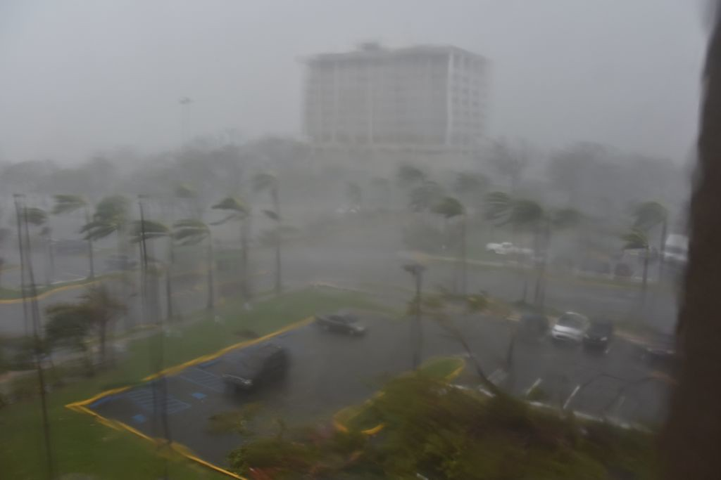 """. Rain and wind hit a parking lot at Roberto Clemente Coliseum in San Juan, Puerto Rico, on September 20, 2017, during the passage of the Hurricane Maria. Maria made landfall on Puerto Rico on Wednesday, pummeling the US territory after already killing at least two people on its passage through the Caribbean. The US National Hurricane Center warned of \""""large and destructive waves\"""" as Maria came ashore near Yabucoa on the southeast coast. / AFP PHOTO / HECTOR RETAMAL        (Photo credit should read HECTOR RETAMAL/AFP/Getty Images)"""