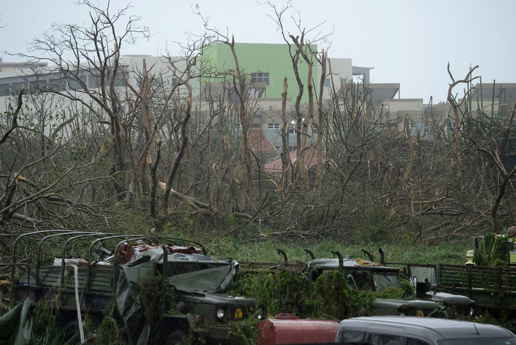. CORRECTS TO REMOVE REFERENCE OF HURRICANE CATEGORY - Trees stripped of their foliage and damaged trucks stand at the principal entrance at the Emergency Management Agency during the impact of Hurricane Maria, which hit the eastern region of the island, in Humacao, Puerto Rico, Wednesday, Sept. 20, 2017. The U.S. National Hurricane Center says Maria has lost its major hurricane status, after raking Puerto Rico. But forecasters say some strengthening is in the forecast and Maria could again become a major hurricane by Thursday. (AP Photo/Carlos Giusti)