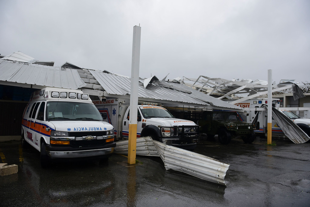 . CORRECTS TO REMOVE REFERENCE OF HURRICANE CATEGORY - Rescue vehicles from the Emergency Management Agency stand trapped under an awning during the impact of Hurricane Maria, which hit the eastern region of the island, in Humacao, Puerto Rico, Wednesday, Sept. 20, 2017. The U.S. National Hurricane Center says Maria has lost its major hurricane status, after raking Puerto Rico. But forecasters say some strengthening is in the forecast and Maria could again become a major hurricane by Thursday. (AP Photo/Carlos Giusti)