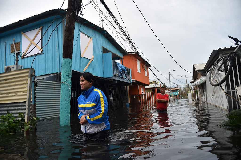 . People walk accros a flooded street in Juana Matos, Puerto Rico, on September 21, 2017 as the country faced dangerous flooding and an island-wide power outage following Hurricane Maria. (HECTOR RETAMAL/AFP/Getty Images)