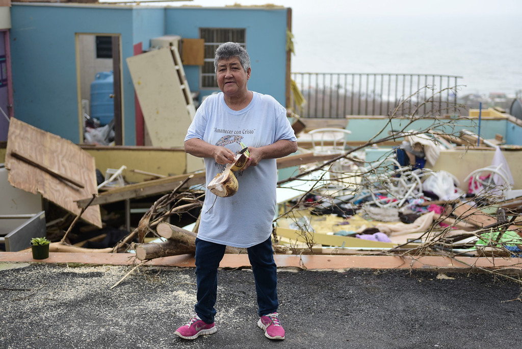 """. \""""Whats important is ones life\"""" says Rufina Fernandez standing in front of her daughters ruined house while eating a coconut a day after the impact of Hurricane Maria, in Yabucoa, Puerto Rico, Thursday, September 21, 2017. As of Thursday evening, Maria was moving off the northern coast of the Dominican Republic with winds of 120 mph (195 kph). The storm was expected to approach the Turks and Caicos Islands and the Bahamas late Thursday and early Friday. (AP Photo/Carlos Giusti)"""