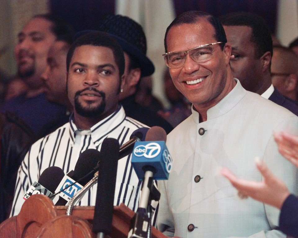 . Rap artist Ice Cube, left, listens as Nation of Islam leader Louis Farrakhan speaks during a news conference at the second National Hip-Hop and Rap Summit on Wednesday, May 14, 1997, in Chicago.  (AP Photo/Beth A. Keiser)