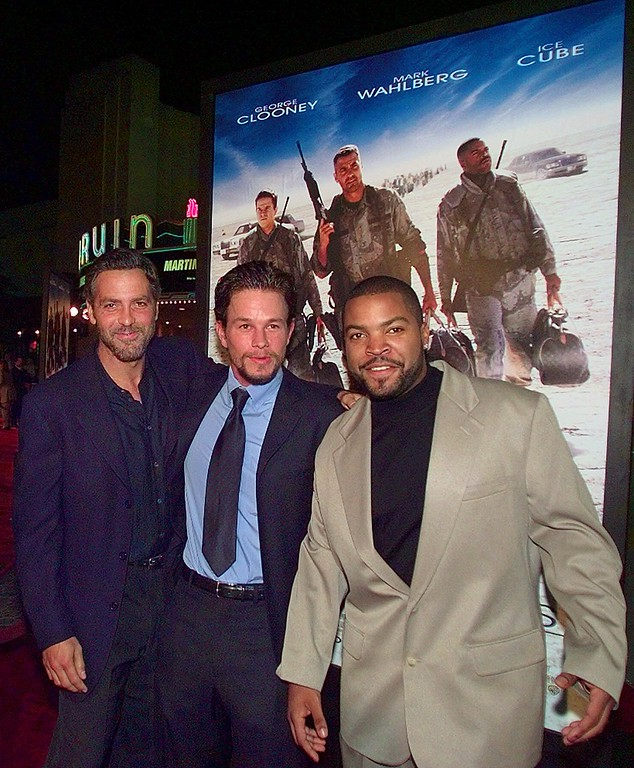 ". Actors George Clooney, left, Mark Wahlberg and Ice Cube, right, arrive at the premiere of Warner Bros.\' ""Three Kings\"" in the Westwood area of Los Angeles, Monday, Sept. 27, 1999. (AP Photo/Michael Caulfield)"