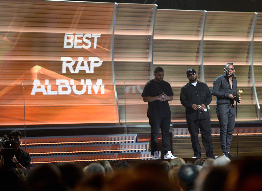 ". LOS ANGELES, CA - FEBRUARY 15:  Singer Kendrick Lamar (R) accepts the award for Best Rap Album for ""To Pimp a Butterfly\"" from actor O\'Shea Jackson Jr. (L) and rapper/actor Ice Cube (C) onstage during The 58th GRAMMY Awards at Staples Center on February 15, 2016 in Los Angeles, California.  (Photo by Kevork Djansezian/Getty Images for NARAS)"