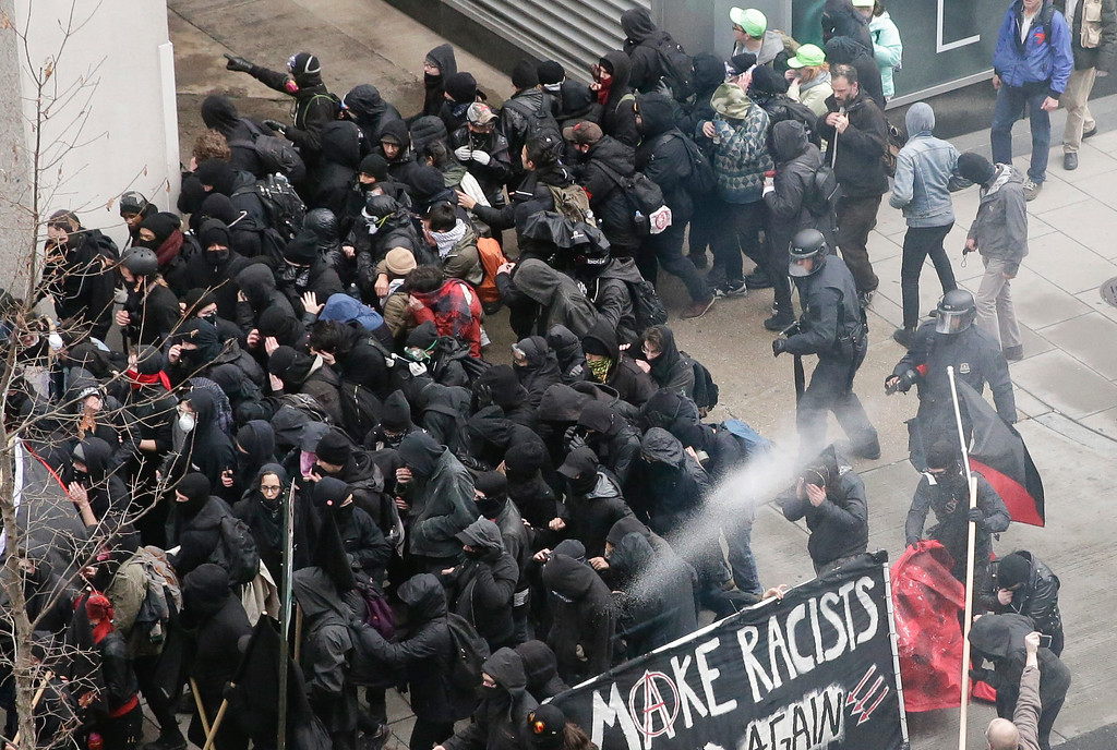 . Police use pepper spray on protesters in Washington, Friday, Jan. 20, 2017, in a chaotic confrontation blocks from Donald Trump\'s inauguration as protesters registered their rage against the new president. (AP Photo/Mark Tenally)