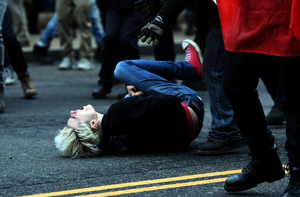 . An anti-Trump protester screams after being hit by a paintball gun fired by Police during clashes in Washington, DC, on January 20, 2107.   Masked, black-clad protesters carrying anarchist flags smashed windows and scuffled with riot police Friday in downtown Washington, blocks away from the route of the parade in honor of newly sworn-in President Donald Trump. Washington police arrested more than 90 people over acts of vandalism committed on the fringe of peaceful citywide demonstrations being held against Trump\'s inauguration. (JEWEL SAMAD/AFP/Getty Images)