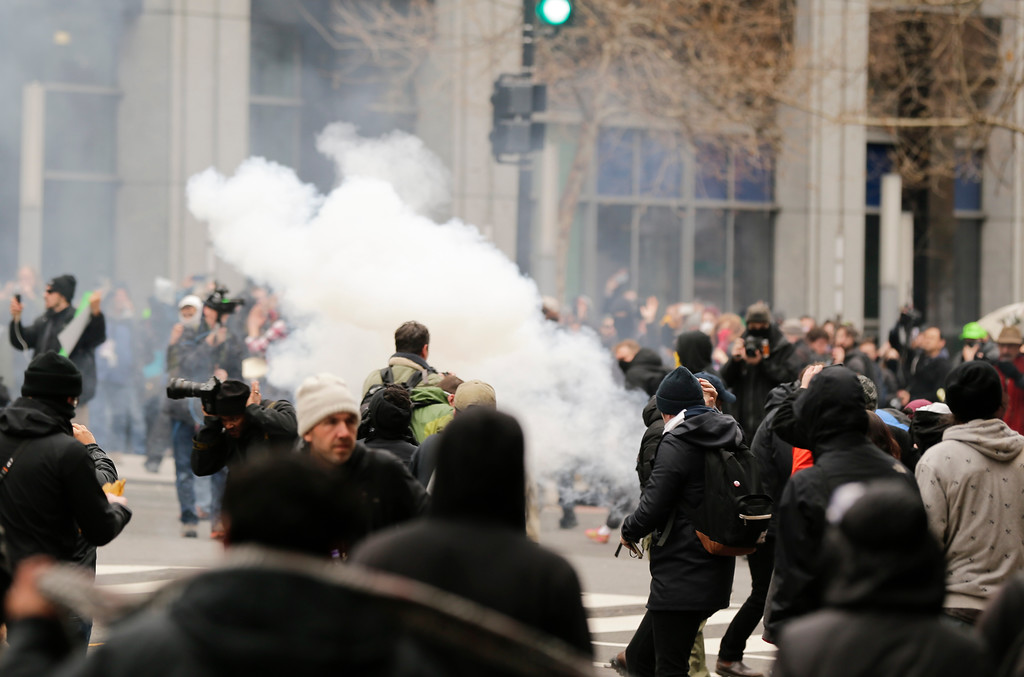 . Police deploy smoke and pepper grenades during clashes with protesters in northwest Washington, Friday, Jan. 20, 2017. (AP Photo/Mark Tenally)