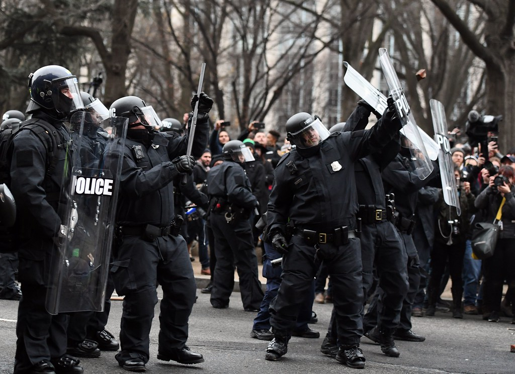 . Police officers shield themselves as an anti-Trump protester throw bricks during clashes in Washington, DC, on January 20, 2107.   Masked, black-clad protesters carrying anarchist flags smashed windows and scuffled with riot police Friday in downtown Washington, blocks away from the route of the parade in honor of newly sworn-in President Donald Trump. Washington police arrested more than 90 people over acts of vandalism committed on the fringe of peaceful citywide demonstrations being held against Trump\'s inauguration. (JEWEL SAMAD/AFP/Getty Images)
