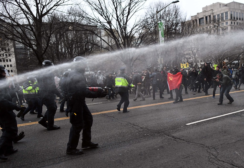 . Police pepper spray at anti-Trump protesters during clashes in Washington, DC, on January 20, 2107.   Masked, black-clad protesters carrying anarchist flags smashed windows and scuffled with riot police Friday in downtown Washington, blocks away from the route of the parade in honor of newly sworn-in President Donald Trump. Washington police arrested more than 90 people over acts of vandalism committed on the fringe of peaceful citywide demonstrations being held against Trump\'s inauguration. (JEWEL SAMAD/AFP/Getty Images)