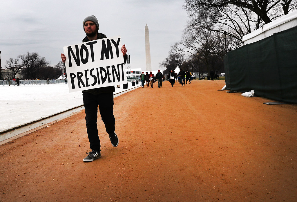 . WASHINGTON, DC - JANUARY 20:  A protester walks on the National Mall for the inauguration of Donald Trump on January 20, 2017 in Washington, DC. Washington and the entire nation are preparing for the transfer of the United States presidency later today as Donald Trump is sworn is as the 45th president Friday.  (Photo by Spencer Platt/Getty Images)