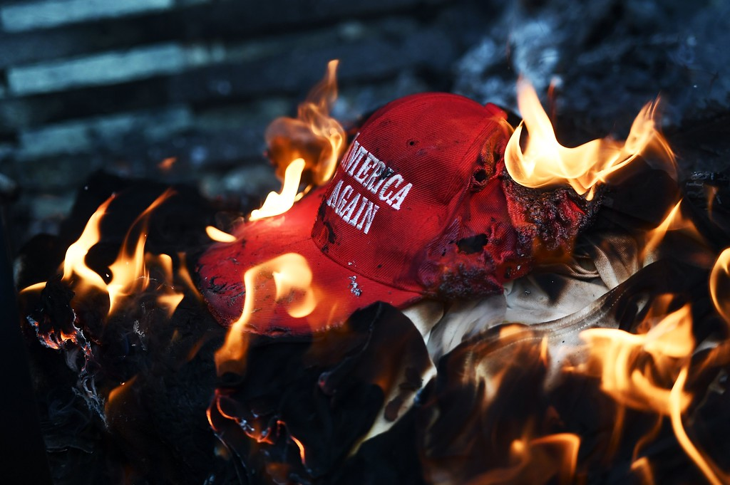 ". Anti-Trump demonstrator set a ""Make America Great Again\"" hat on fire in Washington, DC, on January 20, 2107.    Masked, black-clad protesters carrying anarchist flags smashed windows and scuffled with riot police Friday in downtown Washington, blocks away from the route of the parade in honor of newly sworn-in President Donald Trump.  (JEWEL SAMAD/AFP/Getty Images)"