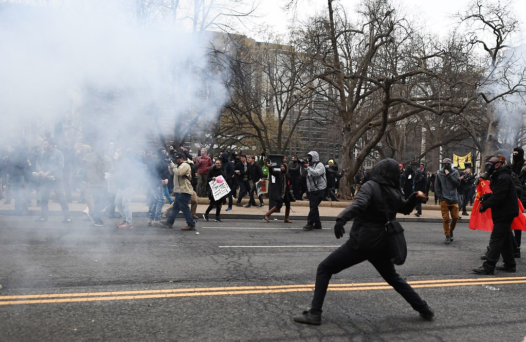 . An anti-Trump protester throws a brick at Police during clashes in Washington, DC, on January 20, 2107.   Masked, black-clad protesters carrying anarchist flags smashed windows and scuffled with riot police Friday in downtown Washington, blocks away from the route of the parade in honor of newly sworn-in President Donald Trump. Washington police arrested more than 90 people over acts of vandalism committed on the fringe of peaceful citywide demonstrations being held against Trump\'s inauguration. (JEWEL SAMAD/AFP/Getty Images)
