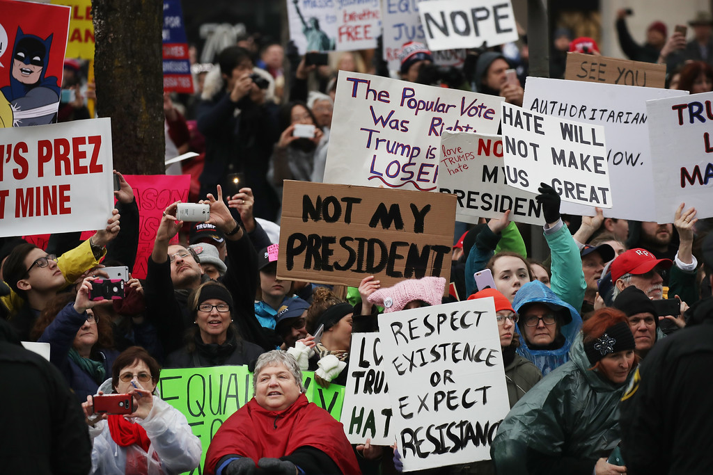 . WASHINGTON, DC - JANUARY 20:  Protesters hold up signs during the Inaugural Parade on January 20, 2017 in Washington, DC. Donald J. Trump was sworn in today as the 45th president of the United States.  (Photo by Drew Angerer/Getty Images)