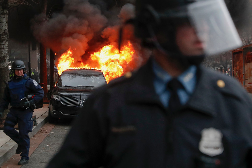 . A parked limousine burns as riot police clear the street during a demonstration after the inauguration of President Donald Trump, Friday, Jan. 20, 2017, in downtown Washington. Protesters registered their rage against the new president Friday in a chaotic confrontation with police who used pepper spray and stun grenades in a melee just blocks from Donald Trump\'s inaugural parade route. Scores were arrested for trashing property and attacking officers.  (AP Photo/John Minchillo)