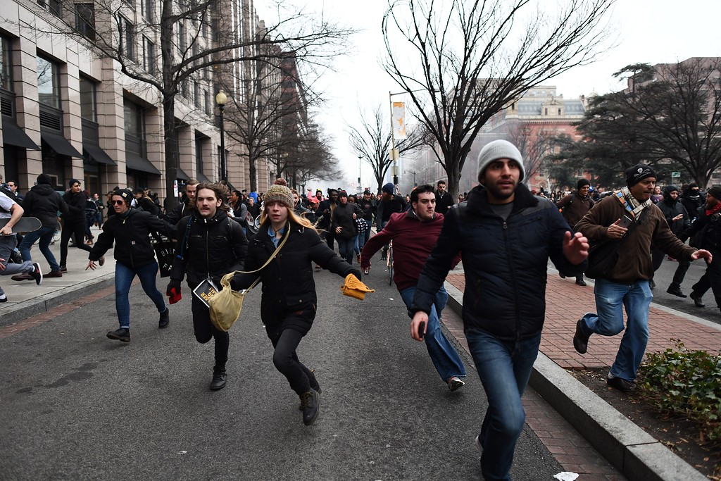 . Anti-Trump protesters flee during clashes with police in Washington, DC, on January 20, 2107.   Masked, black-clad protesters carrying anarchist flags smashed windows and scuffled with riot police Friday in downtown Washington, blocks away from the route of the parade in honor of newly sworn-in President Donald Trump.  (JEWEL SAMAD/AFP/Getty Images)