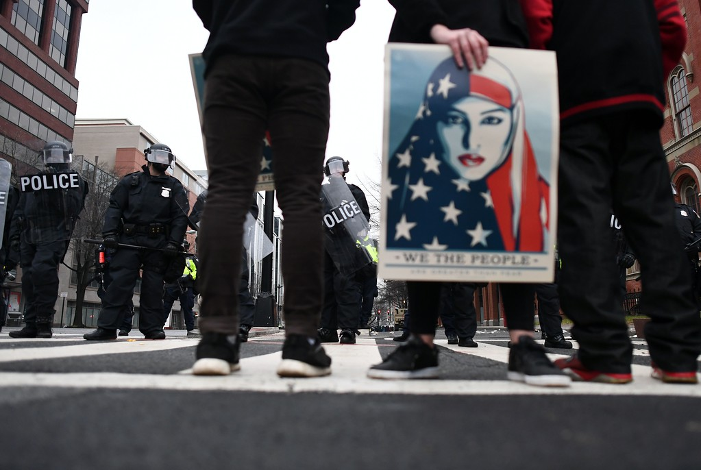 . Police stand guard as anti-Trump protesters shout slogans in Washington, DC, on January 20, 2107.  Masked, black-clad protesters carrying anarchist flags smashed windows and scuffled with riot police Friday in downtown Washington, blocks away from the route of the parade in honor of newly sworn-in President Donald Trump. (JEWEL SAMAD/AFP/Getty Images)