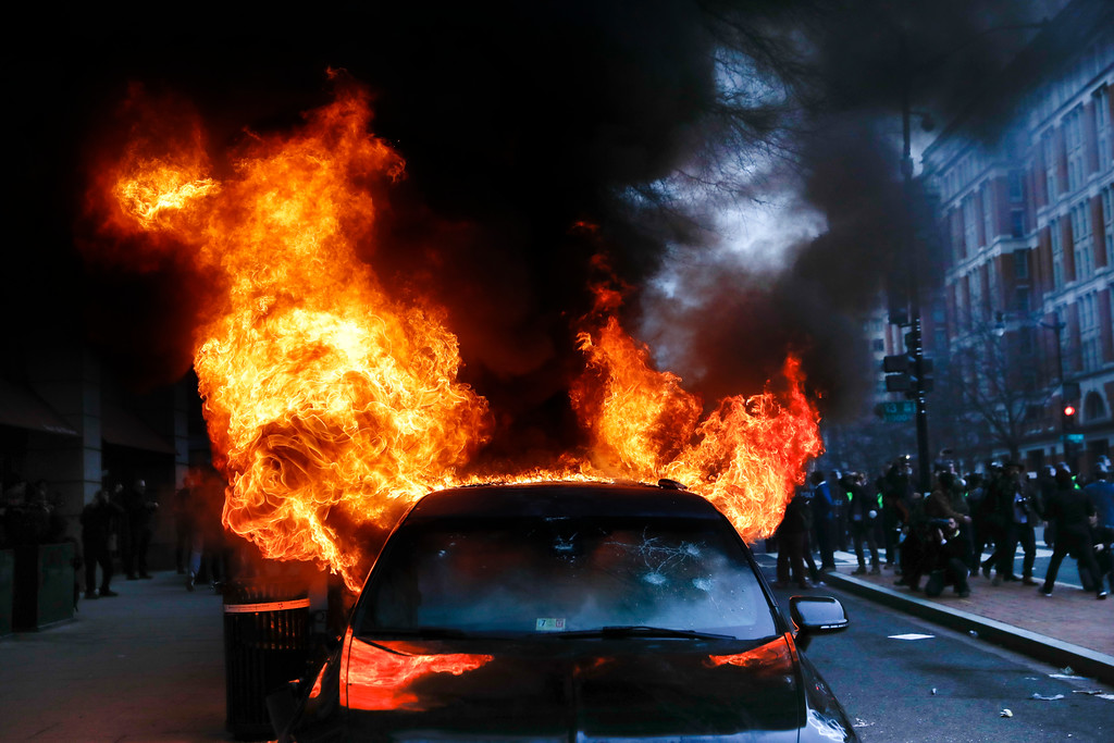 . A parked limousine burns during a demonstration after the inauguration of President Donald Trump, Friday, Jan. 20, 2017, in downtown Washington. Protesters registered their rage against the new president Friday in a chaotic confrontation with police who used pepper spray and stun grenades in a melee just blocks from Donald Trump\'s inaugural parade route. Scores were arrested for trashing property and attacking officers. (AP Photo/John Minchillo)
