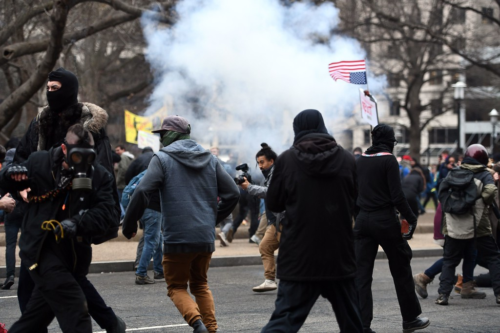 . Anti-Trump protesters flee as police flash-bang grenade explodes during clashes in Washington, DC, on January 20, 2107.   Masked, black-clad protesters carrying anarchist flags smashed windows and scuffled with riot police Friday in downtown Washington, blocks away from the route of the parade in honor of newly sworn-in President Donald Trump. Washington police arrested more than 90 people over acts of vandalism committed on the fringe of peaceful citywide demonstrations being held against Trump\'s inauguration. (JEWEL SAMAD/AFP/Getty Images)