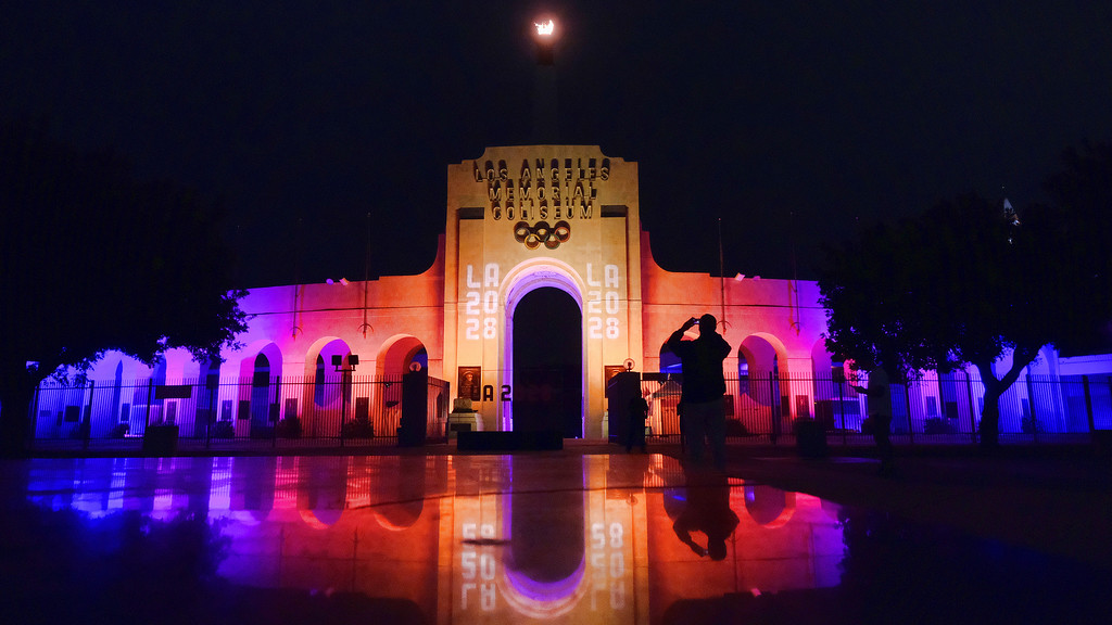 . A visitor takes a photo of a blazing Olympic cauldron at the Los Angeles Memorial Coliseum on Wednesday, Sept. 13, 2017. The cauldron was lit early Wednesday morning at the stadium that was the site of the 1932 and 1984 Olympics. An International Olympic Committee meeting in Peru is to make it official that LA will host in 2028 and that the 2024 Games will go to Paris. (AP Photo/Richard Vogel)