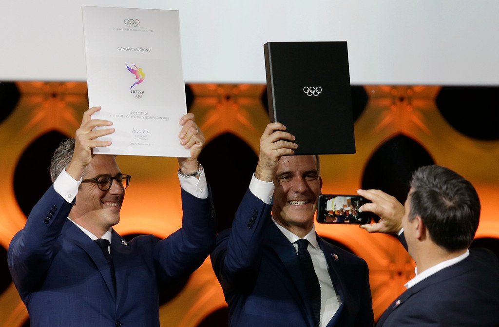 . Los Angeles Mayor Eric Garrett, center, and LA 2024 Chairman Casey Wasserman pose for photos at the end of an International Olympic Committee (IOC) session in Lima, Peru, Wednesday, Sept. 13, 2017. The IOC voted to ratify Los Angeles as the host city of the 2028 Olympic and Paralympic Games and Paris as the host city of the 2024 Games. (AP Photo/Martin Mejia)