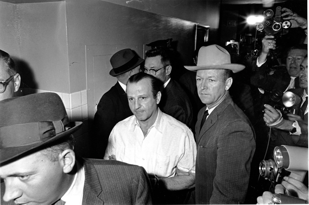 . Nightclub owner Jack Ruby is led through the Dallas city jail on his way to his arraignment in Dallas, Tex. on Nov. 24, 1963.  Ruby was charged for the murder of Lee Harvey Oswald, the man accused with assassinating President John F. Kennedy.  Others are unidentified.  (AP Photo)