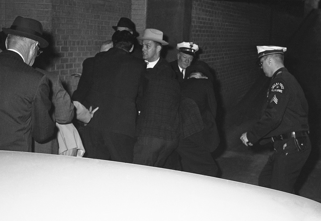 . Plainclothes officers of the Dallas Police Department struggle with a man, identified as nightclub owner Jack Ruby, moments after he shot Lee Harvey Oswald, accused assassin of President Kennedy, outside the Dallas City Jail, Nov. 24, 1963 in Dallas. Ruby is not visible. (AP Photo/David F. Smith)