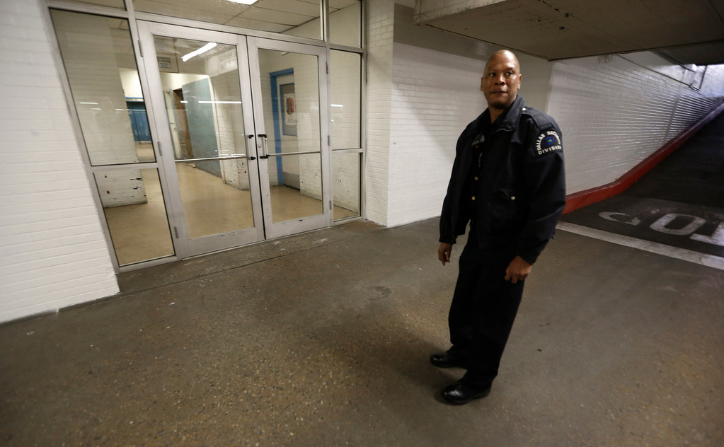 . Sergeant Alex Phillips, with the City of Dallas security division, points out the approximate location where Jack Ruby shot Lee Harvey Oswald in the basement  parking lot of the Dallas Municipal Building Thursday, Nov. 14, 2013, in Dallas. Oswald was held in a jail in this building at 106 S. Harwood. As authorities took him through an underground garage, he was fatally shot by nightclub owner Jack Ruby. The building served as city hall until the late 1970s and included the police department and jail. It still houses Municipal Court but the Oswald-related spots are not accessible to the public. (AP Photo/LM Otero)